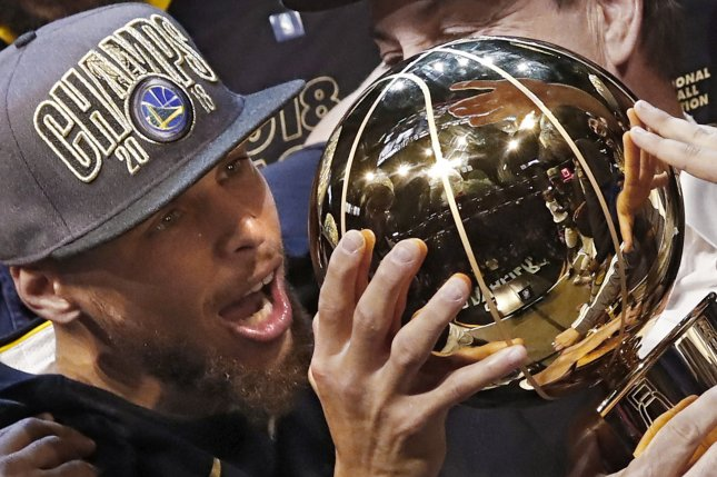 Golden State Warriors guard Stephen Curry holds the NBA Finals trophy after winning Game 4 of the NBA Finals Friday at Quicken Loans Arena in Cleveland. Photo by Larry W. Smith/EPA-EFE