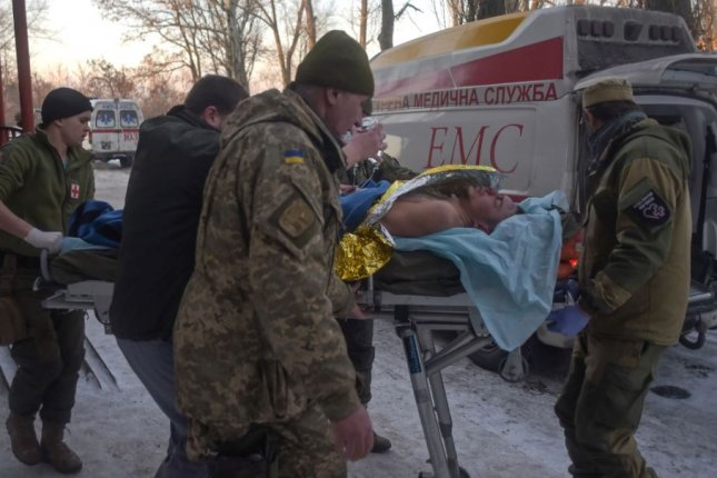 Members of a Ukrainian military medical unit carry an injured soldier from hospital to an ambulance as they prepare to evacuate from the eastern city of Avdiivka near Donetsk on January 30. Heavy artillery and rockets hit residential areas amid a new outburst of fighting between government troops and Russia-backed separatists, prompting NATO officials to denounce Russia and offer Ukraine unanimous support in the conflict. Photo by Markiian Lyseiko/EPA
