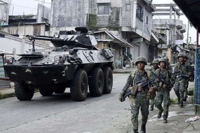 Filipino soldiers advance their position as they pass an armored vehicle during continued fighting Sunday between Islamist militants and government forces in Marawi City in southern Philippines. Photo by Francis R. Malasig/EPA