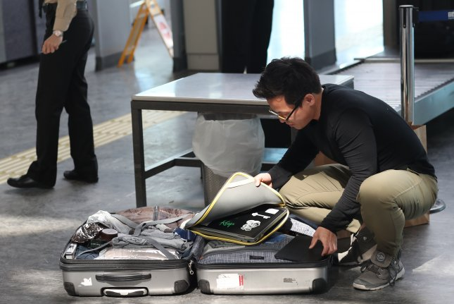 A passenger opens his luggage to show guards his electronic equipment at Turkey's Ataturk Airport. The United States and Britain have banned large electronic devices for passengers in the cabin on flights from some airports in Turkey, the Middle East and North Africa. Photo by Sedat Suna/EPA