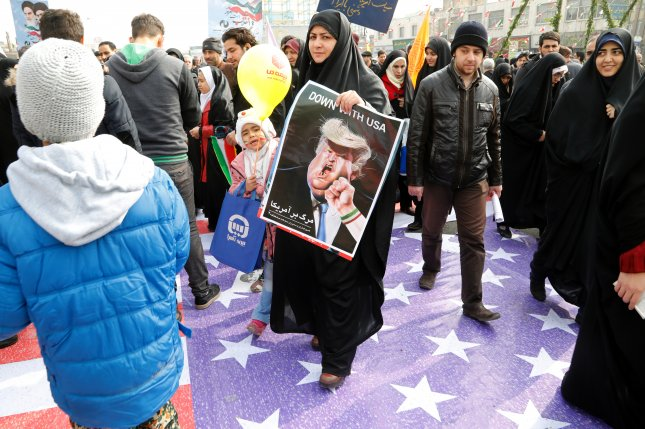 An Iranian woman holds a poster depicting U.S. President Donald Trump at the Azadi Square in Tehran, Iran. Friday, the U.S. Treasury announced sanctions against 9 Iranians and one entity over cyber security. File Photo by Abedin Taherkenareh/EPA-EFE