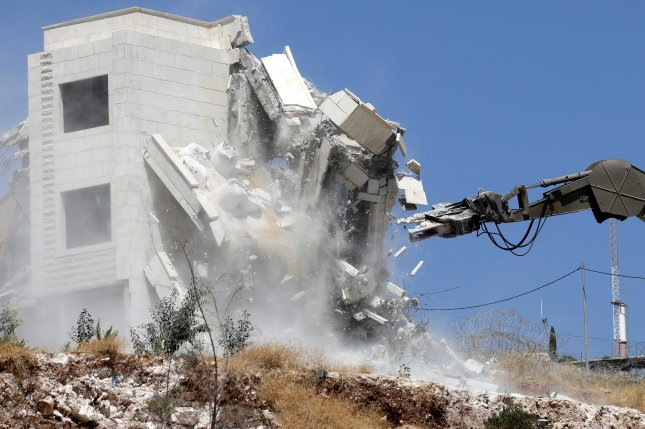 An Israeli army excavator demolishes Palestinian housing Monday in village of Sur Baher, in East Jerusalem. Photo by Abed Al Hashlamoun/EPA-EFE