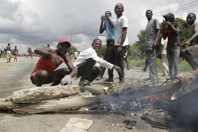 Protesters block a main road in Harare, Zimbabwe, on Monday, after members of the public went onto the streets to protest the recent fuel price increase. Photo by Aaron Ufumeli/EPA