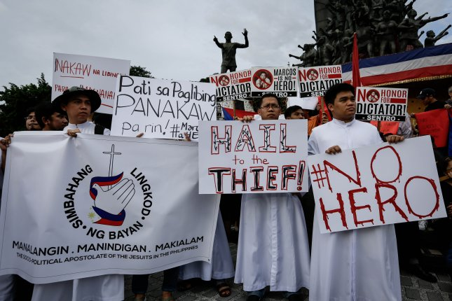 Filipino priests hold placards during a protest against the burial of former dictator Ferdinand Marcos at the People Power Monument in Quezon City, northeast of Manila on November 18, 2016. On September 28, 1989, Marcos died in exile in Hawaii. File Photo by Mark R. Cristino/EPA