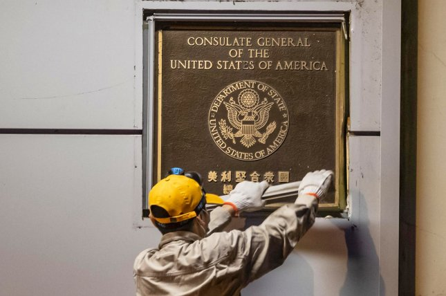 A man attempts to remove a plaque from the front of the US consulate in Chengdu, China, on Sunday. Photo by Alex/Plavevski/EPA-EFE