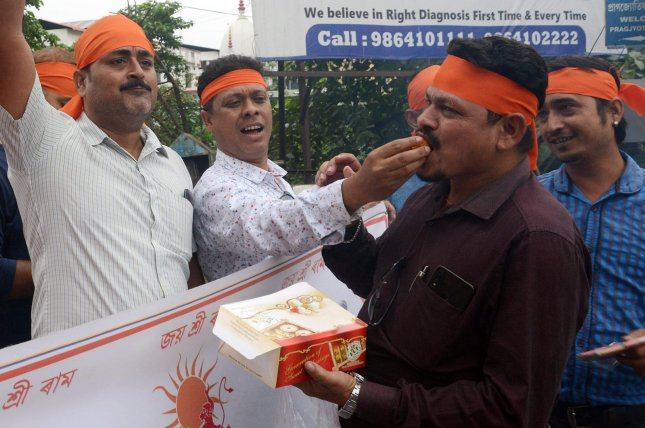 Activists of Hindu organisation Rashtriya Bajrang Dal celebrated the Supreme court verdict allowing Hindus to build a temple on land in Ayodhya after dispute with Muslims over the site by offering sweets to each other after the verdict Saturday. Photo by EPA-EFE