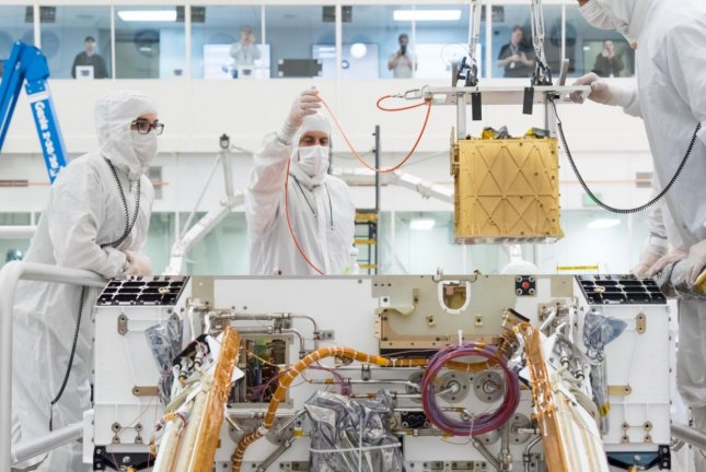 Engineers install the Mars Oxygen In-Situ Resource Utilization Experiment (MOXIE) into the chassis of Mars rover Perseverance on March 20, 2019, at NASA's Jet Propulsion Laboratory, in Pasadena, Calif. Photo courtesy of NASA