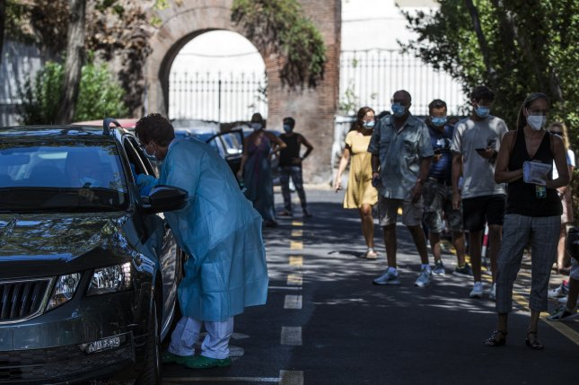 Italian motorists wait in line for their swab samples to be taken for COVID-19 testing by health workers at the drive-in of the San Giovanni hospital in Rome as recommended by the Ministry of Health for all of those who returned from areas at risk. Photo by Angelo Carconi/EPa-EFE