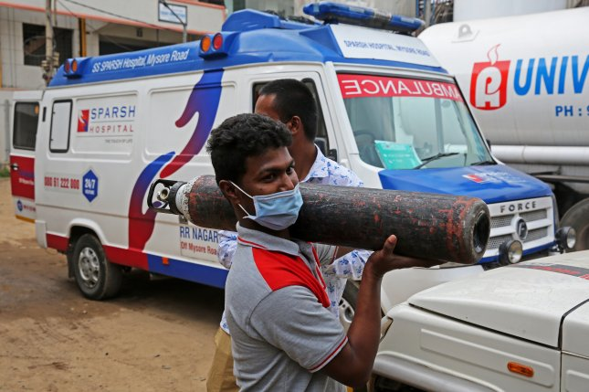 An Indian boy carries an empty oxygen cylinder at an oxygen filling center in Bangalore, India, on Wednesday amid a shortage in the nation during the COVID-19 pandemic. Photo by Jagadeesh Nv/EPA-EFE