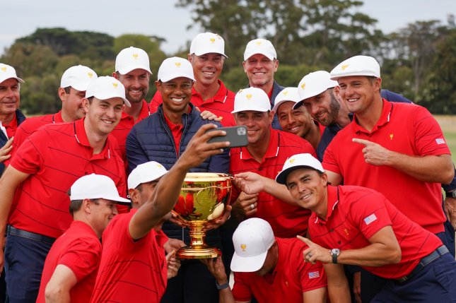 Playing captain Tiger Woods and his U.S. teammates celebrate with the Presidents Cup after they defeated the International team during Sunday at the Royal Melbourne Golf Club in Australia. Photo by Scott Barbourt/EPA-EFE
