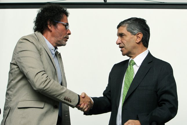 Member of FARC Felix Antonio Munoz Lascarro, left, also known as Pastor Alape, and Colombia's High Counselor for Post-Conflict, Human Rights and Security Rafael Pardo shake hands during a press conference in Bogota on January 27, 2017. The Colombian government and FARC announced a program to replace about 200 square miles of illegal crops, mainly coca plants, during its first year of implementation in 40 municipalities of the country. Photo by Mauricio Duenas Castaneda/EPA