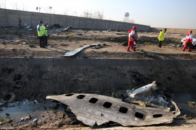 Emergency services personnel walk amidst the wreckage after an Ukraine International Airlines Boeing 737-800 carrying 176 people crashed near Imam Khomeini Airport in Tehran in this January photo. Iran has sent the black box of the flight to Paris for analysis. File Photo by Abedin Taherkenareh/EPA-EFE