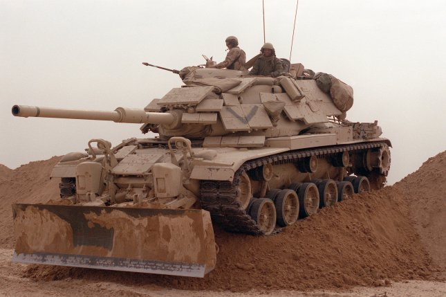 Marines from Company D, 2nd Tank Battalion, drive their M-60A1 main battle tank over a sand berm on Hill 231 on February 24, 1991, while rehearsing their role as part of the ground campaign in Kuwait during Operation Desert Storm. The tank is fitted with reactive armor and an M-9 bulldozer kit. File Photo by SSgt. M.D. Masters/U.S. Department of Defense