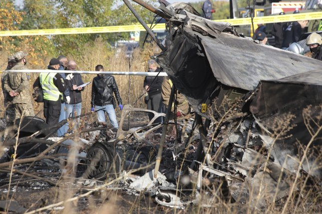 Rescuers inspect the crash site of an Antonov An-26 plane near Chuguyev city Kharkiv oblast, Ukraine, on Saturday. Photo Sergey Khrupov/EPA-EFE