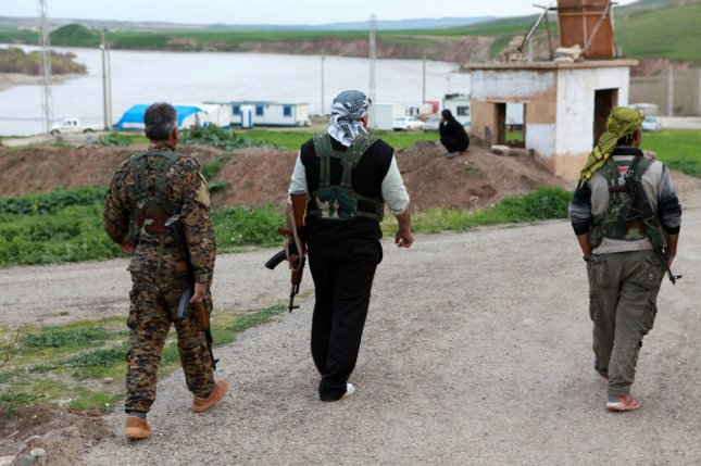 Members of the Kurdish People's Protection Units, or YPG, walk on a road in northern Syria on March 19, 2013. Three heavily armed British citizens of Iraqi-Kurdish descent were arrested in Greece on Saturday under suspicion of smuggling a large amount of weapons and ammunition into Turkey. Photo by fpolat69 / Shutterstock.com