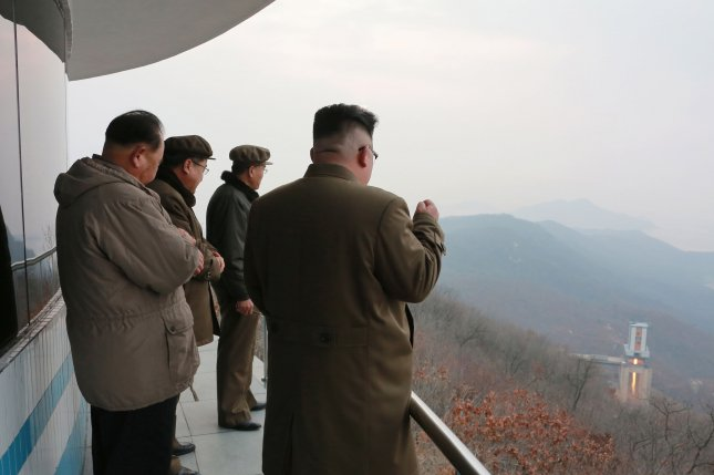 "North Korean leader Kim Jong Un (R) in a photo released in March 2017, watches the test of a high-thrust rocket engine at Sohae satellite launch facility. The regime defended its ""peaceful"" satellite launches in a law journal, a South Korean press report said Monday. File Photo by KCNA/EPA"