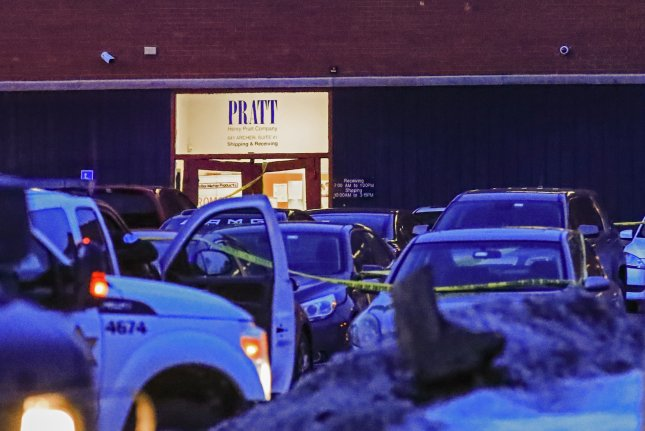 Yellow crime tape is stretched across a parking lot after a shooting at the Henry Pratt Company office in Aurora, Ill., on Friday night. Photo by Tannen Maury/EPA