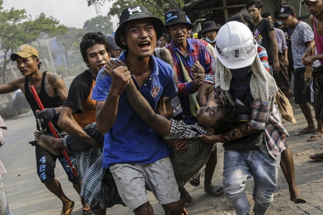 An injured demonstrator is carried to receive medical attention during a protest against the military coup in Hlaing Thar Yar Township, on the outskirts of Yangon, Myanmar, On Sunday. Anti-coup protests continued despite the intensifying violent crackdowns on demonstrators by security forces. Photo by EPA-EFE