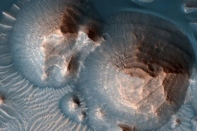 Several craters in Arabia Terra on Mars are filled with layered rock. The image is processed to highlight the geologic formations. Photo courtesy of NASA/JPL-Caltech/University of Arizona