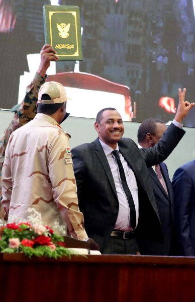 Sudan's Forces of Freedom and Change coalition leader Ahmad al-Rabiah (R) flashes a victory sign after signing the power sharing agreement (green document at Top) with Sudan's General and Vice President of Sudanese Transitional Military Council Mohamed Hamdan Dagalo (L), as international guests watch in Khartoum, Sudan, Saturday. Photo by Morwan Ali/ EPA-EFE