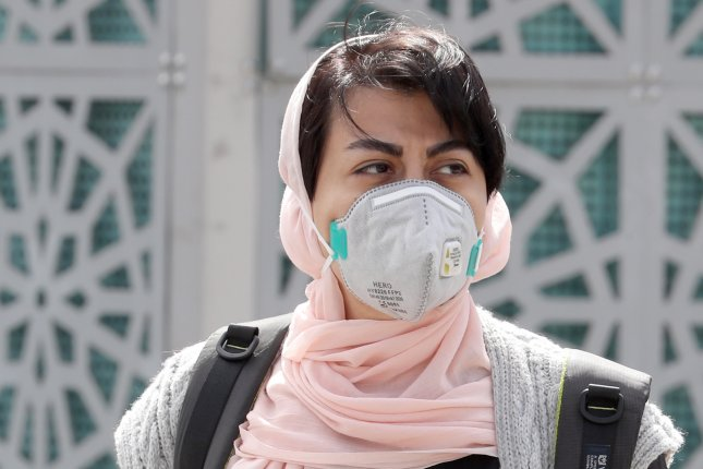 An Iranian woman wearing a face mask walks in Tehran on Monday. Photo by Abedin Taherkenareh/ EPA-EFE