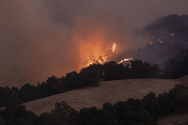 The Kincade Fire burns in the hills above Geyserville, Calif. After a delayed start to the wet season for the state, moisture from former Tropical Storm Raymond combined with a separate storm system are forecast to join forces this week to supply much-needed rain. Photo by Peter Dasilva/EPA-EFE/