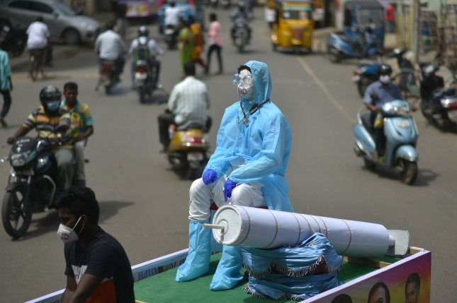Volunteers carry a mannequin in a personal protective equipment suit on a cycle rickshaw on Friday in Chennai, India, during an awareness campaign against the spread of COVID-19. Photo by Idrees Mohammed/EPA-EFE