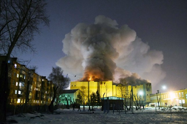 Smoke rises over the Zimnaya Vishnya shopping center in Kemerovo, Russia, Monday after a fire erupted and killed dozens of people -- including several children, officials said. Four people were arrested in connection to the blaze. Photo by Alexander Patrin/A42.Ru/EPA-EFE