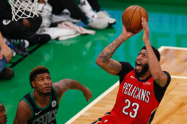 New Orleans Pelicans star Anthony Davis (R) makes a shot while defended by Boston Celtics forward Marcus Smart (L) during the NBA match between the Boston Celtics and the New Orleans Pelicans on December 10 at the TD Garden in Boston. Photo by C.J. Gunther/EPA-EFE