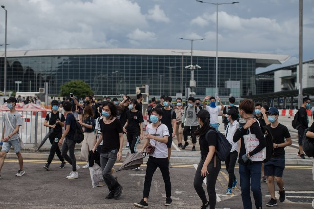 Protesters disperse as riot police movein at Hong Kong International Airport in Hong Kong after protesters shut down transportation to and from the area. Photo by Jerome Favre/EPA
