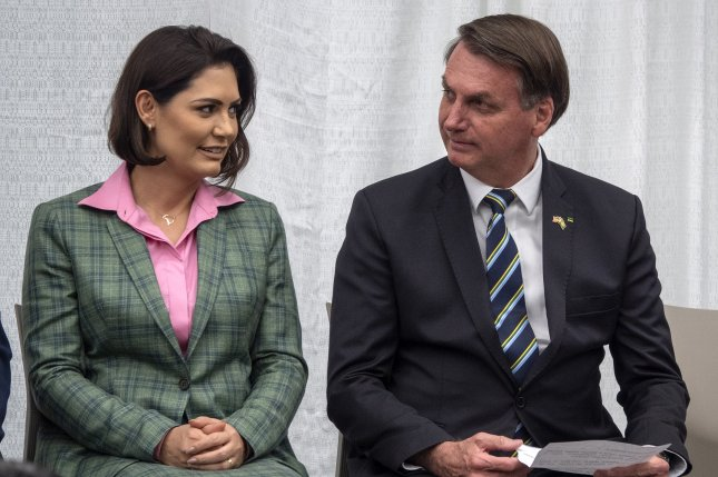 Brazilian President Jair Bolsonaro speaks with his wife Michelle Bolsonaro during a meeting with the Brazilian community in Florida at Miami Dade College Medicine Campus on March 9. Michelle Bolsonaro tested positive for coronavirus on Thursday. File Photo by Cristobal Herrera/EPA-EFE