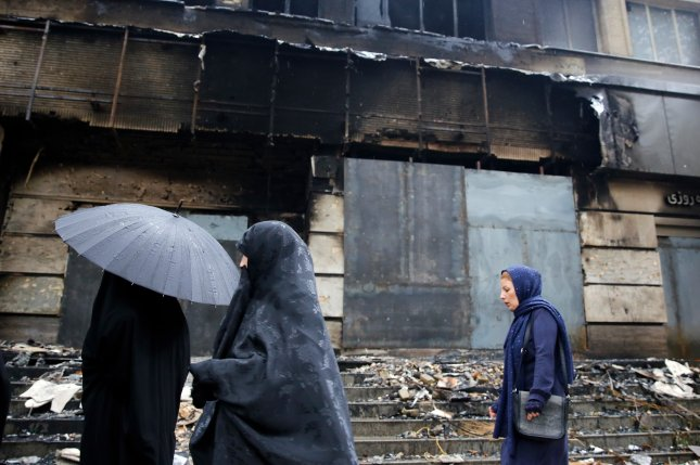 Iranian women pass a branch of the Melat Bank that was burned during the protests in Shahriar, Alborz province, Iran, on November 20. Photo by Abedin Taherkenareh/EPA-EFE