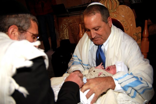 Jewish infant Shalev Dadon from Jerusalem during his brit milah, a traditional circumcision ceremony representing the covenant between the Children of Israel and God, on June 1, 2008 in Jerusalem, Israel. Photo by ChameleonsEye/Shutterstock