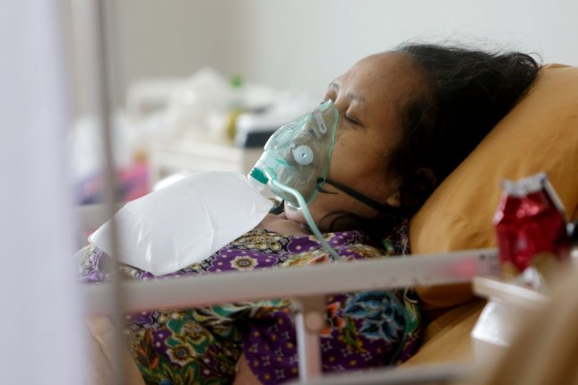A COVID-19 patient breathes through a ventilator at Bogor City Hospital, Indonesia, in June. File Photo by Adi Weda/EPA-EFE