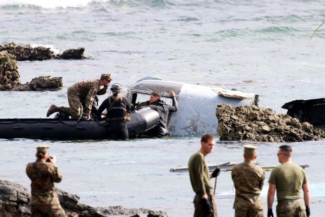 U.S. military personnel inspect the wreckage of the tilt-rotor MV-22 Osprey aircraft that crash landed in the sea on December 13, off the coast of Nago, Okinawa Island, southwestern Japan, on December 14, 2016. Following the request of Japanese government, U.S. forces decided to ground all Osprey tilt-rotor military aircrafts. Photo by Hitoshi Maeshiro/Eueopean Pressphoto Agenc