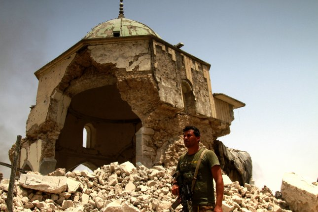 An Iraqi soldier stands next to the destroyed Great Mosque of al-Nuri in the old city area western Mosul, Iraq. The UAE and United Nations said Tuesday $50 million will be spent to rebuild it. File photo by EPA-EFE
