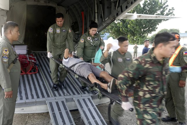 Philippine Air Force personnel assist a wounded man aboard a military C-295 transport plane at Edwin Andrews Air Base in Zamboanga City, southern Philippines. He was among the victims of the twin bombings before a Sunday mass at Cathedral of Our Lady of Mount Carmel in Jolo in the Mindanao region. Photo by Laurenz Castillo/EPA