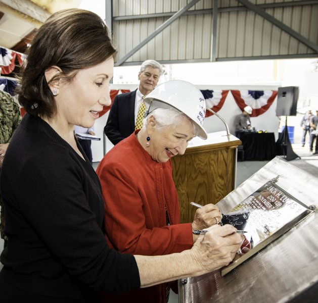 Catherine B. Reynolds and Ruby Lucas, sponsors of the USS Jack H. Lucas, trace their initials onto a steel plate that will be welded inside the Arleigh Burke-class Flight III guided missile destroyer during construction. Photo by Derek Fountain/Huntington Ingalls Industries