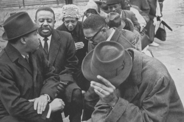 Dr. Martin Luther King Jr. and Dr. Ralph Abernathy (left, behind King) pray with fellow demonstrators protesting for the right to vote in February 1965, Selma, Ala. Photo by Gary Haynes/UPI