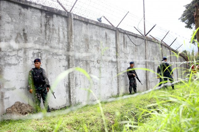 Armed Filipino policemen stand guard next to the wall of a prison facility where detainees escaped in Kidapawan City, North Cotabato province, in the Philippines, on Wednesday. At least 21 inmates have been recaptured by authorities, officials said Thursday. Photo by Althea Ballentes/European Pressphoto Agency
