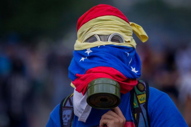 A protester wearing a gas mask is seen during clashes with the Venezuelan National Guard in Caracas on Monday. At least 134 people remain detained after arrests related to protests that began on March 30. The Venezuelan opposition on Tuesday called on security forces to end their repression of peaceful demonstrators. Photo by Miguel Gutierrez/EPA