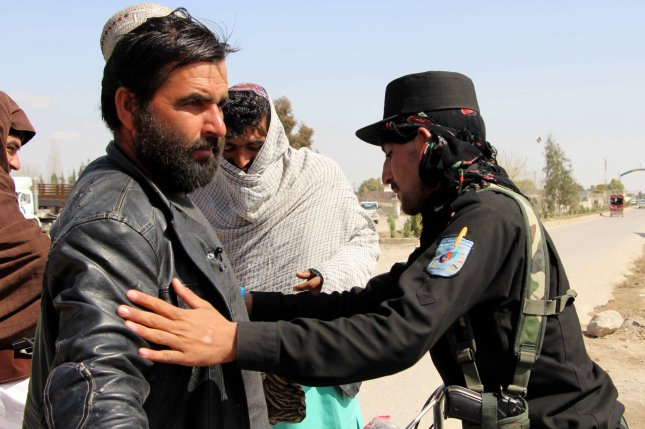 An Afghan security official checks people at the checkpoint in Helmand province, Afghanistan, on Tuesday. At least 11 policemen were killed by the Taliban in an attack. Photo by Watan Yar/EPA