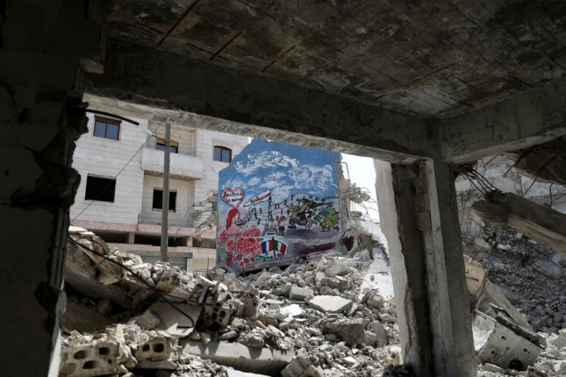Graffiti is seen on damaged building in war-torn Idlib province in northwest Syria, on April 23. Photo by Yahya Nemah/EPA-EFE