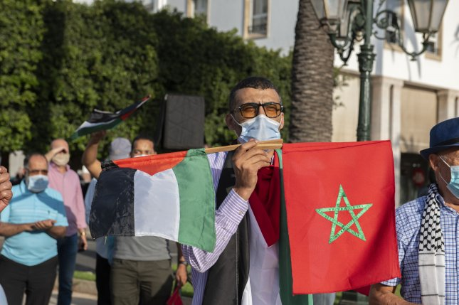 A man holds Palestinian and Moroccan flags during a protest on September 18 opposing the normalization of relations with Israel and showing Palestinian support, in front of Parliament in Rabat, Morocco. File Photo by Jalal Morchidi/EPA-EFE