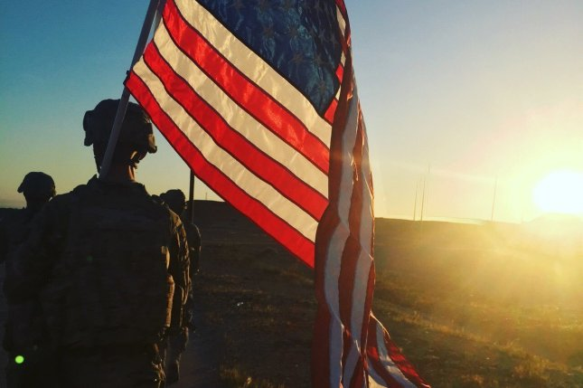 A U.S. Army Sgt. carries the American Flag at Al Asad Air Base, Iraq, on May 3, 2016. Secretary of Defense Ash Carter confirmed on Tuesday the killing of an U.S. Navy SEAL by enemy fire near Mosul. Photo by Spc. Middleton/U.S. Army National Guard/UPI