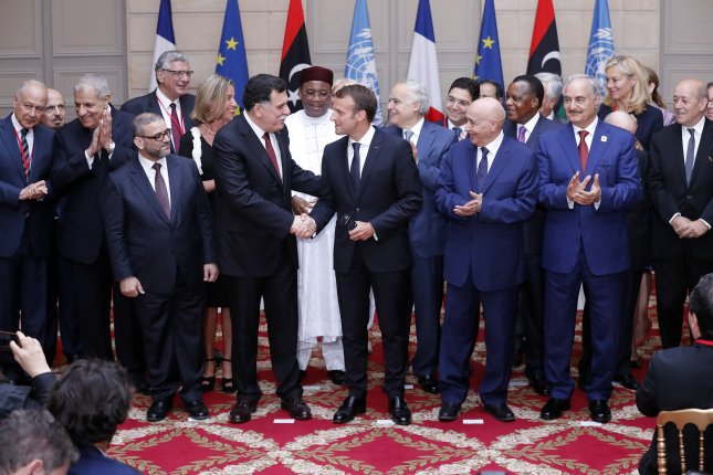 Libyan Prime Minister Fayez al-Sarraj (center left) shakes hands with French President Emmanuel Macron Tuesday at the International Conference on Libya in Paris, France. Photo by Etienne Laurent/Pool/EPA