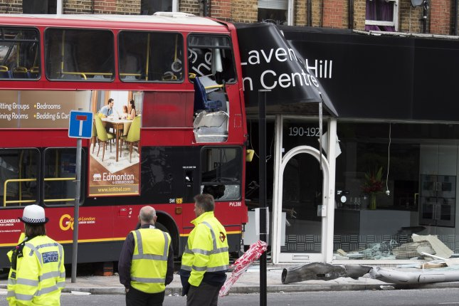 Emergency crews look at a double-decker bus after it crashed into a shop in Clapham, south London, on Thursday. Two women trapped on the upper deck were rescued by paramedics. Photo by Will Oliver/EPA