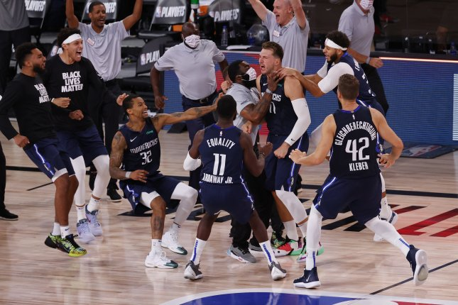 Dallas Mavericks star Luka Doncic (77) is mobbed by his teammates after hitting a 3-point shot at the buzzer against the Los Angeles Clippers during overtime in Game 4 of their first-round playoff series Sunday at the ESPN Wide World of Sports Complex near Orlando, Fla. Photo by John G. Mabanglo/EPA-EFE