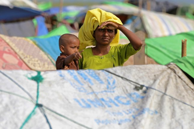 A Rohingya refugee holds her child in a makeshift camp in Bangladesh. Photo by Hein Htet/EPA-EFE