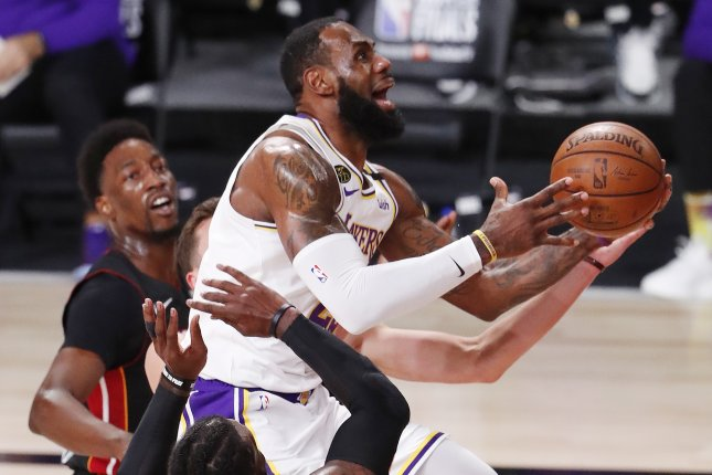 Los Angeles Lakers forward LeBron James (C) drives to the basket between Miami Heat forwards Jae Crowder (B) and Bam Adebayo (L) during the first quarter in Game 6 of the NBA Finals on Sunday at the ESPN Wide World of Sports Complex near Orlando, Fla. Photo by Erik S. Lesser/EPA-EFE